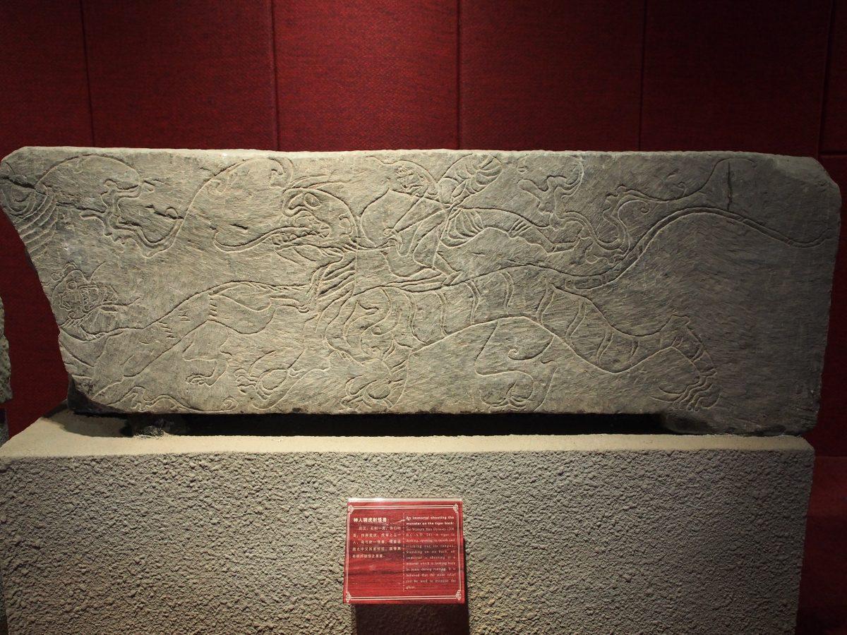 西汉·神人骑虎射怪兽画像石